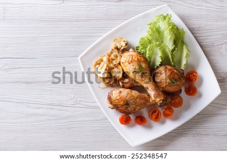 Fried chicken legs with mushrooms and tomatoes on a plate. horizontal view from above  - stock photo