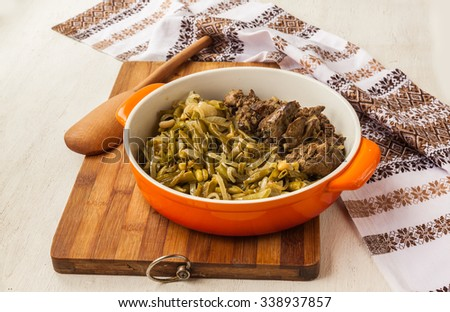 Fried chicken liver and garnish green green beans with onion in a pan on the kitchen table - stock photo