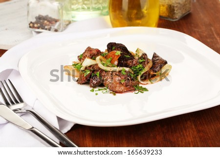 Fried chicken livers on plate on wooden table close-up - stock photo