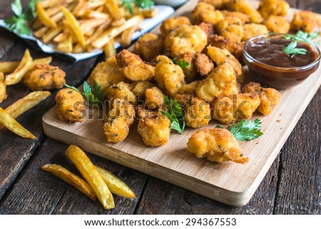 Fried chicken meat and french fries served on wooden board,selective focus  - stock photo