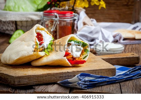 Fried chicken meat with vegetables in pita bread. Selective focus.  - stock photo