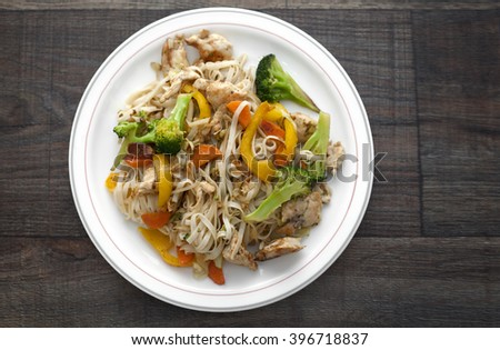 Fried chicken noodles with vegetables broccoli, cabbage, paprika and carrots. - stock photo