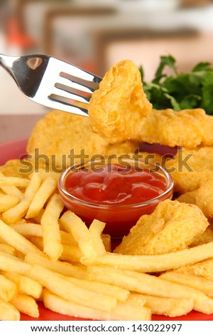 Fried chicken nuggets with french fries and sauce on table in cafe - stock photo