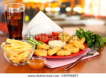 Fried chicken nuggets with vegetables,cola,french fries and sauce on table in cafe - stock photo