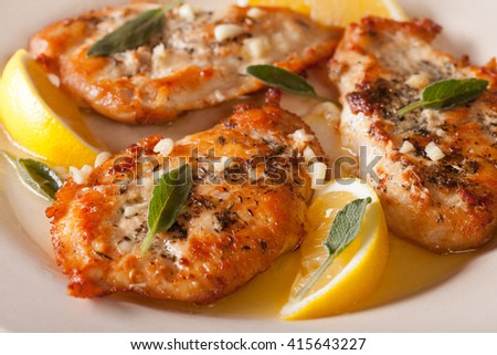 fried chicken steaks with sage, garlic and butter on a plate macro. Horizontal