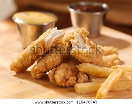 fried chicken strips with french fries and sauce. - stock photo