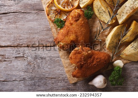 Fried chicken wings dipped in batter, with potato and lemon horizontal view from above  - stock photo