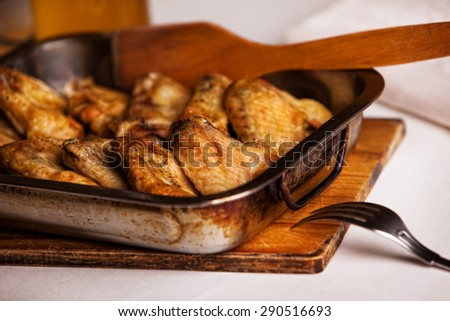 Fried chicken wings in the oven-pan - stock photo