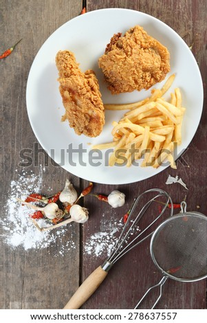 fried chicken wings with french fries on wood table. view from above. - stock photo