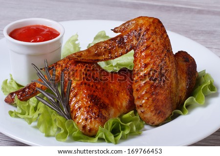 Fried chicken wings with rosemary, lettuce and tomato sauce on the table - stock photo