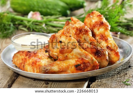 Fried chicken wings with sauce on wooden table - stock photo