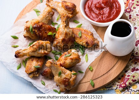 Fried chicken wings with sauces on wooden board, close up, selective focus, top view - stock photo