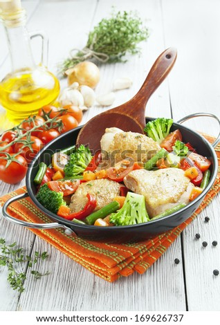 Fried chicken with vegetables in the  pan - stock photo