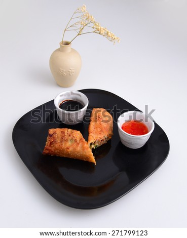 Fried Chinese egg roll on black plate with ceramic pots of chili & soy dipping sauces & clay vase with baby's breath flowers in the background - stock photo