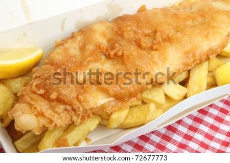 Fried cod & chips in cardboard takeaway carton. - stock photo