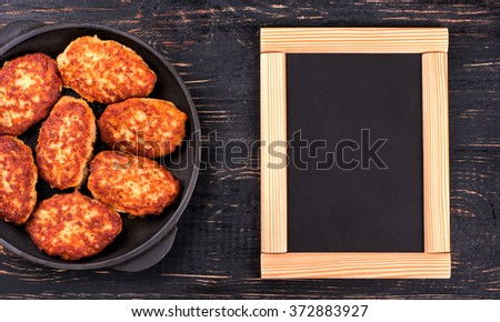 Fried cutlets in a pan with an empty table for menus and recipes, top view - stock photo