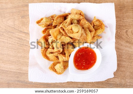 Fried dumpling and sauce on wood table - stock photo