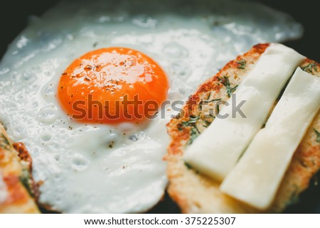 fried egg and bread with cheese on the pan, close-up - stock photo