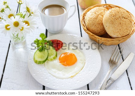 Fried egg and cup of coffee with milk - stock photo