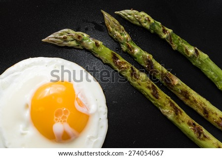 Fried egg and roasted fresh  asparagus in black plate - stock photo
