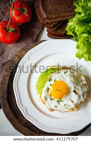 Fried egg, avocado and cheese on whole wheat toast. Overhead view - stock photo