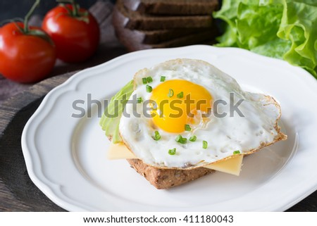 Fried egg, avocado and cheese on whole wheat toast. Selective focus - stock photo