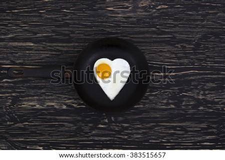 Fried egg Heart shape on the pan - stock photo