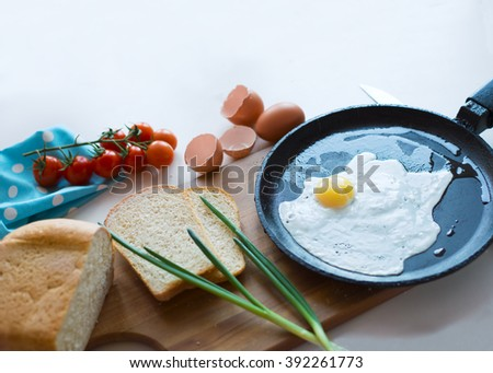 Fried egg in a frying pan, green onion, cherry tomatoes, toast. Simple hearty breakfast. - stock photo