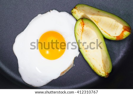 Fried egg in a frying pan with slices of avocado - stock photo