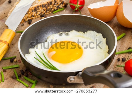 fried egg in a pan on a wooden background  - stock photo
