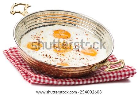 Fried egg in copper egg pan isolated on white background - stock photo