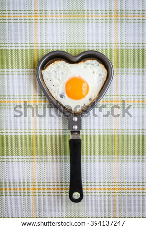 fried egg in the shape of a heart in a frying pan - stock photo
