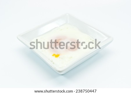 fried egg in white bowl isolated before white background  - stock photo
