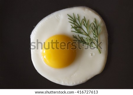 Fried egg on a black background, or in a pan. Flat position, top view. Spinach - stock photo
