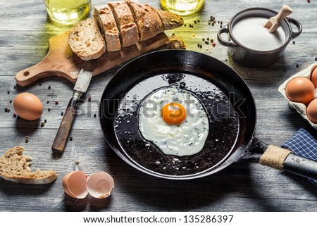 Fried egg on a pan served with homemade bread - stock photo