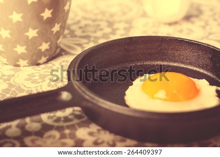Fried egg on a small black frying pan, selective focus - stock photo