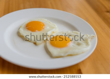 Fried egg on a white dish at breakfast. - stock photo