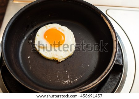 Fried egg on frying pan. - stock photo