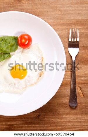 Fried egg served on a wooden table with tomato and fresh herbs - stock photo