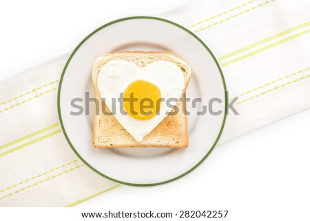 Fried egg sunnyside in heart shape on plate, top view. I love breakfast. Fresh modern image language. Culinary arts.  - stock photo