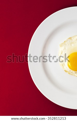 Fried egg. Top half view of white dish with fried egg on red background. - stock photo