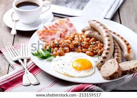 Fried egg with beans in tomato sauce, bacon and grilled sausages with a cup of coffee and morning newspaper. Traditional English breakfast. - stock photo