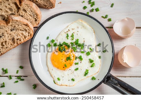 Fried egg with chives served with bread - stock photo