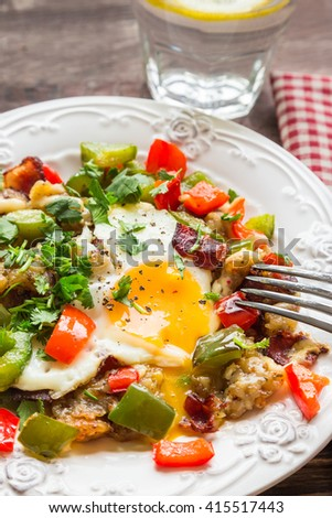 Fried egg with pepper, bacon, potatoes and cilantro on rustic wooden background. Selective focus. - stock photo