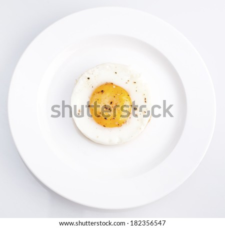Fried egg with salt and pepper served on a white plate - stock photo