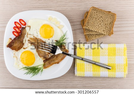Fried eggs and bacon with dill, chili peppers, garlic in plate, fork on napkin and bread on wooden table, top view - stock photo