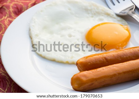 Fried eggs and sausage on a white porcelain plate - stock photo