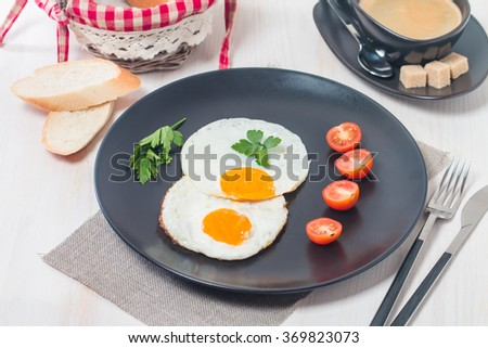 Fried eggs and tomato on a black plate with coffee on white background - stock photo
