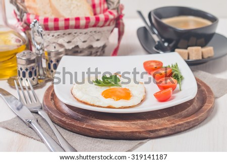 Fried eggs and tomato on a white plate with coffee on white background - stock photo
