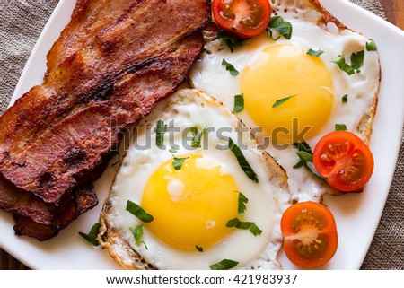 fried eggs fried bacon and cherry tomatoes on a white plate sprinkled with parsley - stock photo